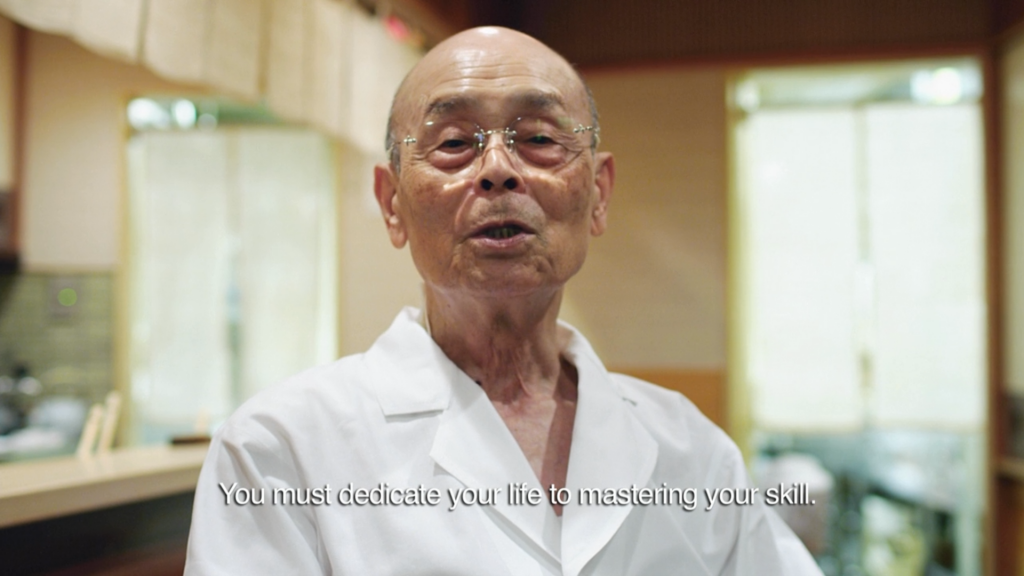 A screenshot from the movie 'Jiro Dreams of Sushi'. Jiro is saying 'You must dedicate your life to mastering your skill.'.
